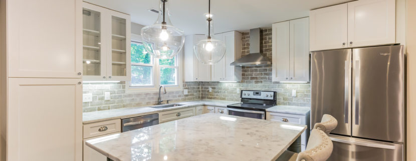 "AFTER: Custom Designed Kitchen with True Reclaimed Brick Backsplash, Designer Lighting, ""New Super White"" Stone Counter tops, and an over-sized Island with Reclaimed Legs from an old Farmhouse Porch Column,"