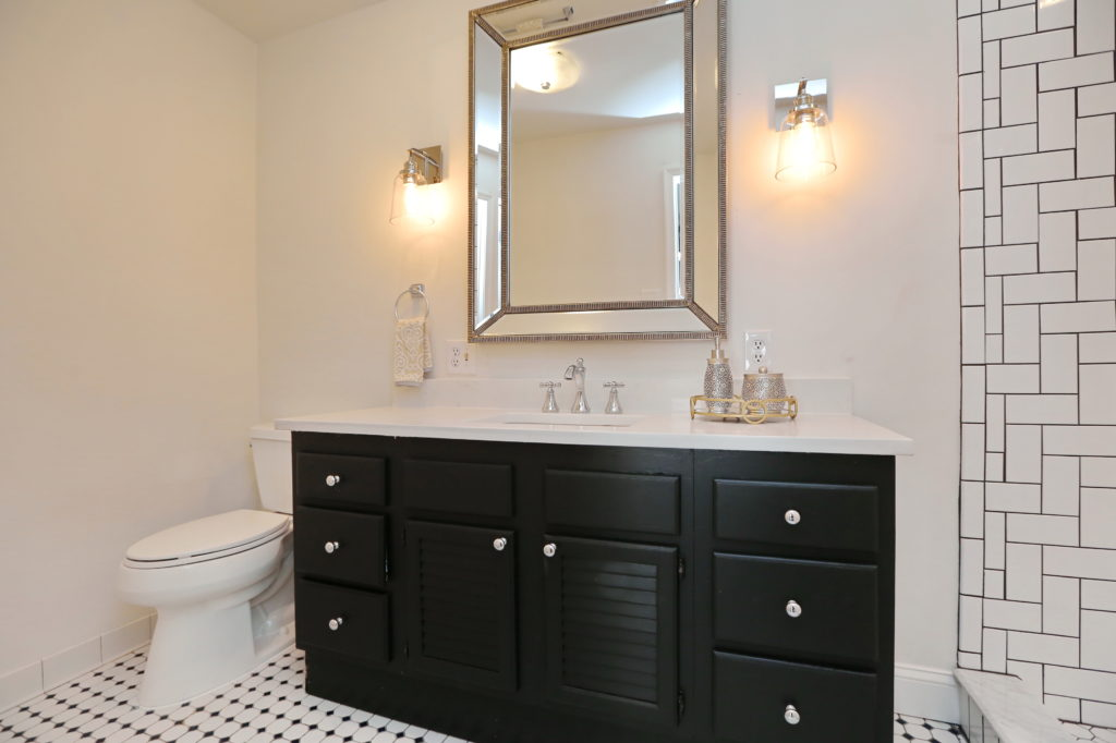 Master Bathroom with Painted Vanity, Black & White Checked Tile, Chrome Sconces, & High End Mirror